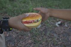 Dos muchachos que comen las hamburguesas Imagen de archivo libre de regalías