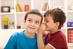 Dos muchachos que comparten un secreto Imagen de archivo libre de regalías