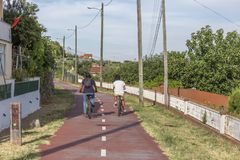 Dos muchachos que completan un ciclo en la trayectoria peatonal del ciclo, con las lámparas de calle, cielo azul como fondo y veg imagen de archivo libre de regalías