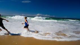 Dos muchachos que corren y que salpican en agua en la playa