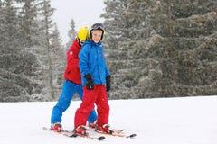 Dos muchachos que disfrutan de vacaciones del esquí del invierno Foto de archivo libre de regalías