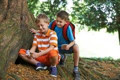 Dos muchachos que encuentran el artículo mientras que Geocaching en bosque foto de archivo libre de regalías