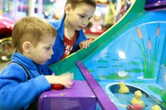Dos muchachos que juegan al juego de arcada imagen de archivo