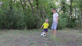 Dos muchachos que juegan con el balón de fútbol en el parque almacen de metraje de vídeo
