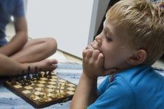 Dos muchachos que juegan el juego de mesa del ajedrez y al un muchacho que piensa muy difícilmente Fotos de archivo libres de regalías
