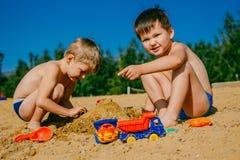 Dos muchachos que juegan en la arena en la playa fotos de archivo libres de regalías