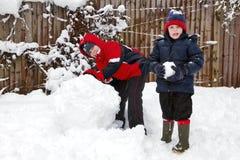 Dos muchachos que juegan en la nieve Imagen de archivo libre de regalías