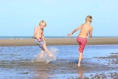 Dos muchachos que juegan en la playa Imágenes de archivo libres de regalías