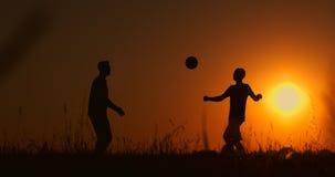 Dos muchachos que juegan a f?tbol en la puesta del sol Silueta de los ni?os que juegan con una bola en la puesta del sol El conce metrajes