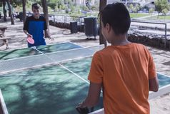 Dos muchachos que juegan a ping-pong en la calle Imágenes de archivo libres de regalías