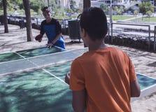 Dos muchachos que juegan a ping-pong en la calle Imagen de archivo libre de regalías
