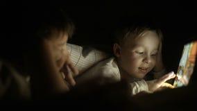 Dos muchachos que mienten en cama en la noche y que usan el cojín almacen de metraje de vídeo