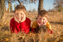 Dos muchachos que mienten en parque del otoño Fotografía de archivo