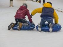 Dos muchachos que minimizan la colina al aire libre de la tubería de la nieve Imágenes de archivo libres de regalías