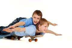 Dos muchachos que montan en un patín Fotos de archivo
