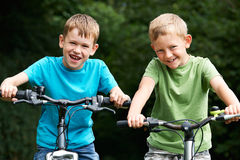 Dos muchachos que montan las bicis juntas Imagen de archivo libre de regalías