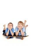 Dos muchachos que presentan en un patín Foto de archivo libre de regalías
