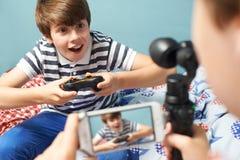 Dos muchachos que registran el blog del juego en dormitorio Imagenes de archivo