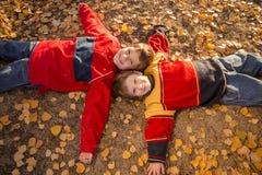 Dos muchachos que se acuestan en parque del otoño Fotos de archivo libres de regalías
