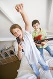 Dos muchachos que se colocan en jugar de la cama Imágenes de archivo libres de regalías