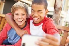 Dos muchachos que se sientan en banco en la alameda que toma Selfie Foto de archivo libre de regalías