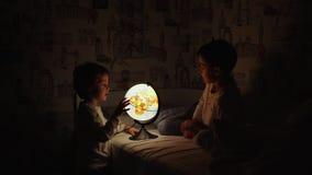 Dos muchachos que se sientan en cama en la noche que gira el globo y los sueños de viajar almacen de metraje de vídeo