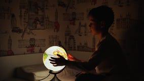 Dos muchachos que se sientan en cama en la noche que gira el globo y los sueños de viajar almacen de video