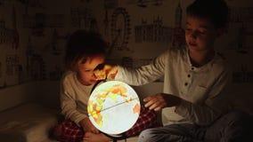 Dos muchachos que se sientan en cama en la noche que gira el globo y los sueños de viajar metrajes