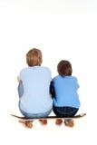 Dos muchachos que se sientan en un patín Imagenes de archivo