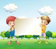Dos muchachos que sostienen un letrero vacío Fotografía de archivo libre de regalías