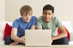 Dos muchachos que usan la computadora portátil en el país Imágenes de archivo libres de regalías