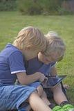 Dos muchachos rubios con la tableta. Foto de archivo