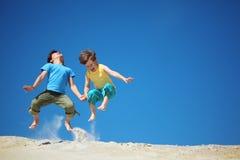 Dos muchachos saltan en la arena imagenes de archivo