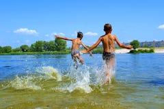 Dos muchachos se ejecutan en el agua Imágenes de archivo libres de regalías