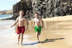 Dos muchachos se están ejecutando en la playa Imágenes de archivo libres de regalías