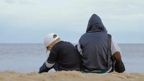 Dos muchachos se sientan en la playa y miran el mar metrajes