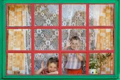 Dos muchachos se sientan por la ventana Foto de archivo libre de regalías