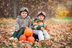 Dos muchachos, sentándose en una maleta Fotos de archivo libres de regalías