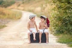 Dos muchachos, sentándose en una maleta vieja grande del vintage, jugando con a Foto de archivo