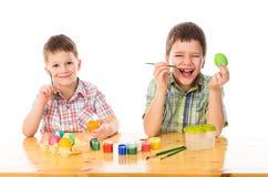 Dos muchachos sonrientes que pintan los huevos de Pascua Imagen de archivo
