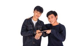 Dos muchachos tailandeses en chaqueta de los vaqueros están mirando el reloj foto de archivo