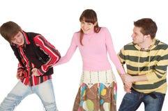 Dos muchachos tiran de la muchacha en diversas direcciones por imagen de archivo