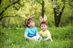 Dos muchachos y amigos de los niños en oídos del conejito de pascua durante el huevo tradicional cazan en jardín de la primavera, Imagen de archivo