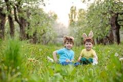 Dos muchachos y amigos de los niños en oídos del conejito de pascua durante el huevo tradicional cazan en jardín de la primavera, Imágenes de archivo libres de regalías