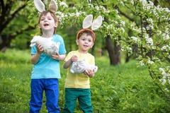 Dos muchachos y amigos de los niños en oídos del conejito de pascua durante el huevo tradicional cazan en jardín de la primavera, Foto de archivo libre de regalías