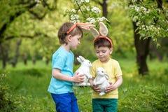 Dos muchachos y amigos de los niños en oídos del conejito de pascua durante el huevo tradicional cazan en jardín de la primavera, Fotos de archivo