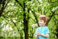 Dos muchachos y amigos de los niños en oídos del conejito de pascua durante el huevo tradicional cazan en jardín de la primavera, Fotografía de archivo