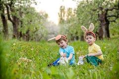Dos muchachos y amigos de los niños en oídos del conejito de pascua durante tra Imagenes de archivo