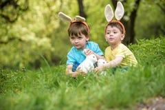 Dos muchachos y amigos de los niños en oídos del conejito de pascua durante tra Imagen de archivo libre de regalías