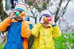 Dos muchachos y amigos de los niños que hacen que el huevo de Pascua tradicional caza Foto de archivo libre de regalías